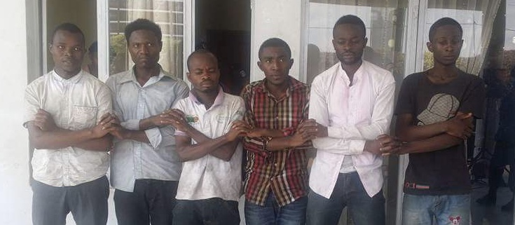 Nos 6 camarades, les mains entrecroisées en signe de force et de dignité, lors de leur présentation à la parade de la Police le 25 octobre 2016, un jour après leur arrestation et leur torture sur ordre de certains officiers. En partant de la gauche vers la droite, Faustin Dunia est le 5ème, Glody Ntambwe le 6ème, et Jacques Muhindo le deuxième.